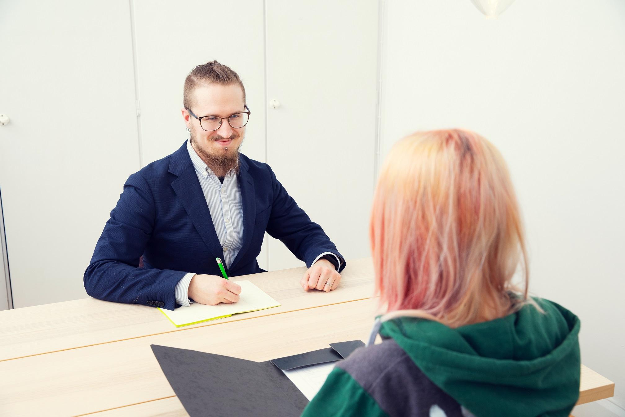 Silmälasipäinen mies pikkutakissa haastattelu punahiuksista nuorta pöydän äärellä.