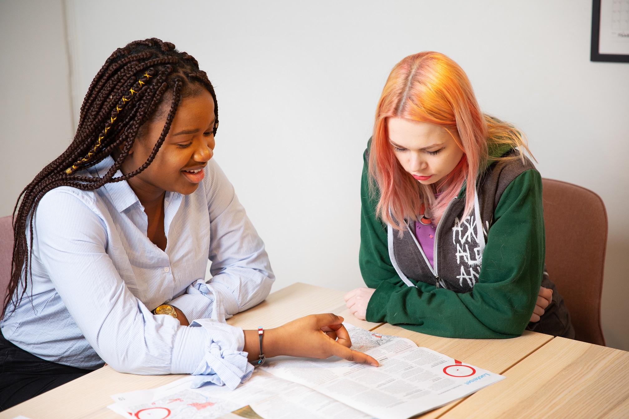 Kaksi nuorta tutkii sanomalehteä