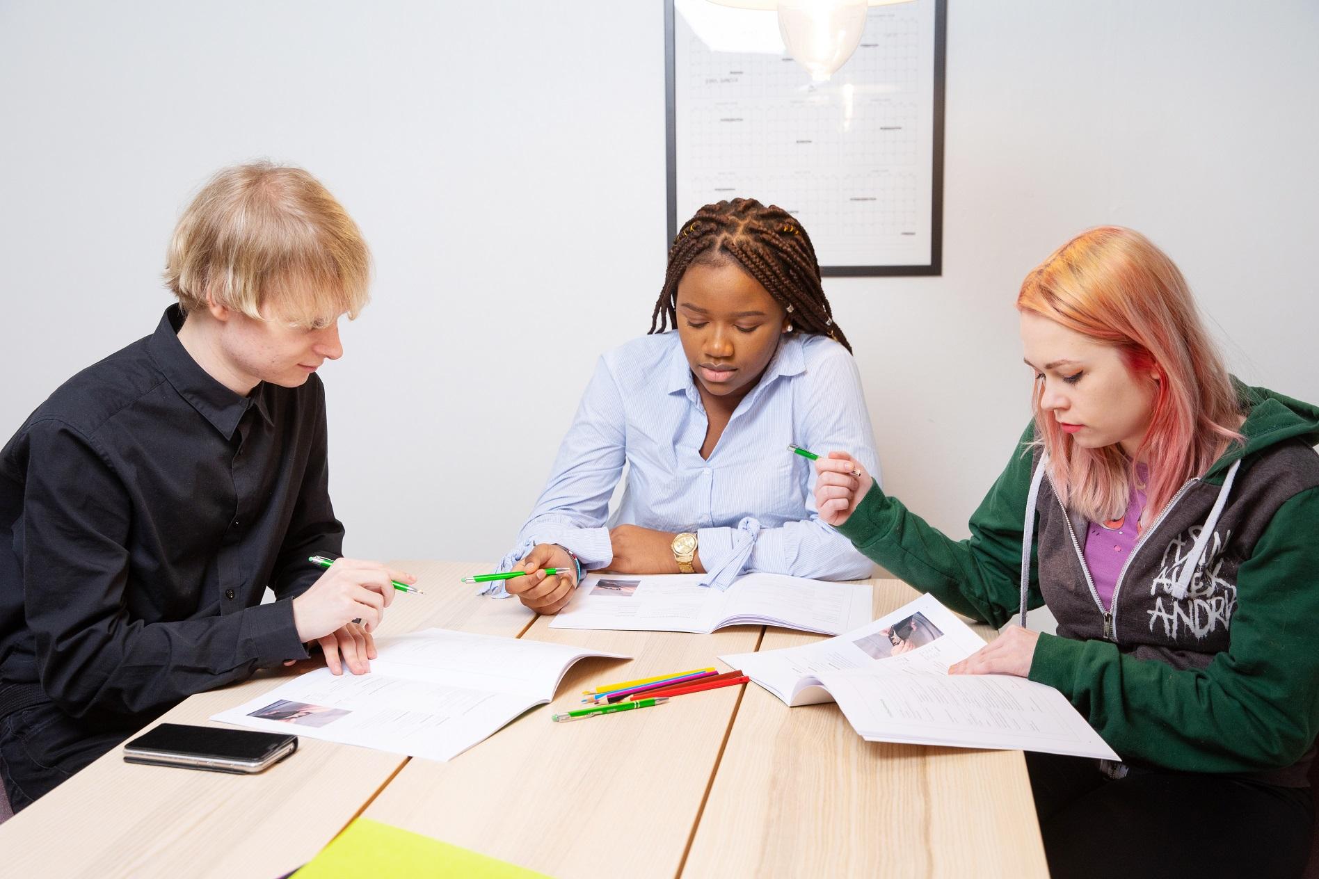 Kolme nuorta tekee tehtäviä pöydän ääressä