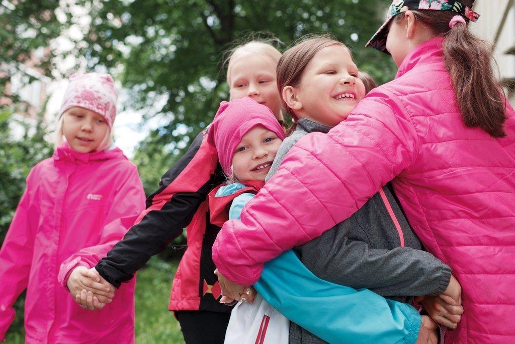 Ryhmä lapsia halaa yhdessä