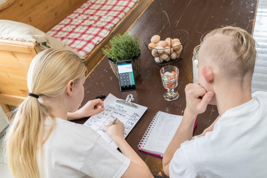 Kaksi henkilöä kuvattu selkäpäin. He istuvat pöydän ääressä ja kirjoittavat suunnitelmaa.