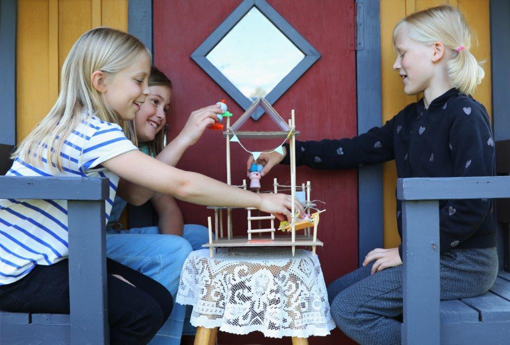 Kolme lasta istuu penkeillä vastakkain. He leikkivät välissä olevalla pöydällä olevalla avoimella nukkekodilla.