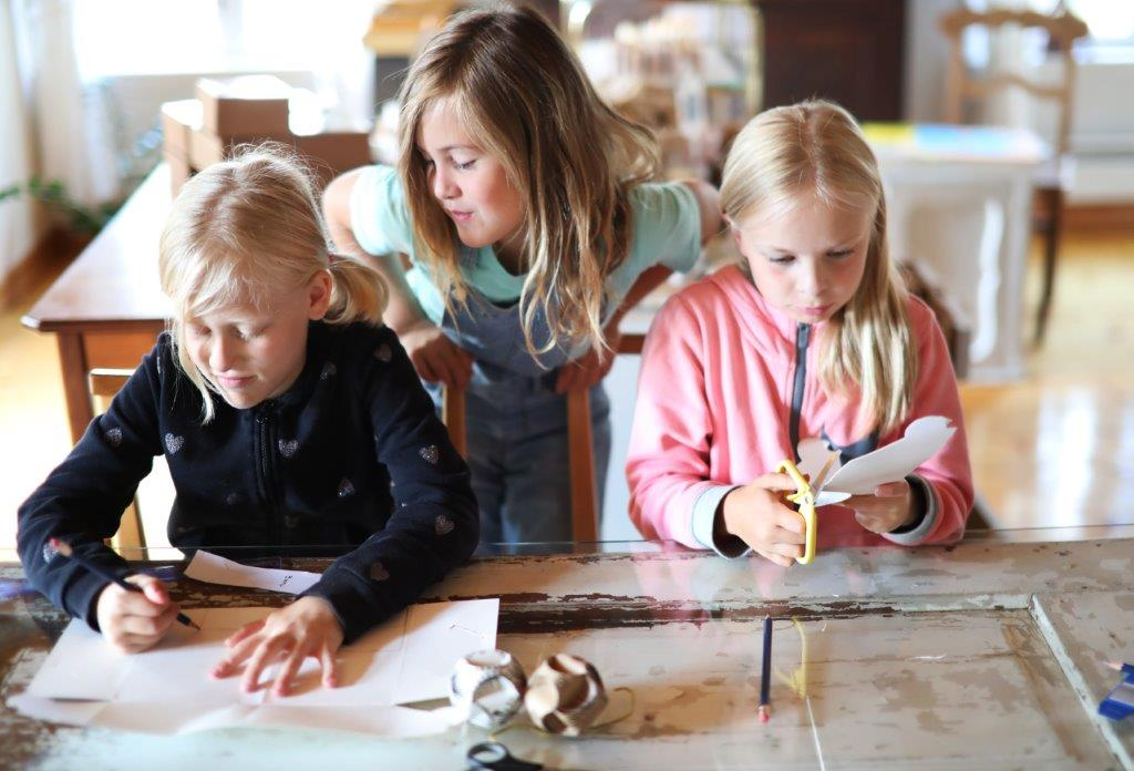Kolme lasta. Yksi piirtää. Toinen leikkaa paperia saksilla. Kolmas kurkistaa toisten takaa.