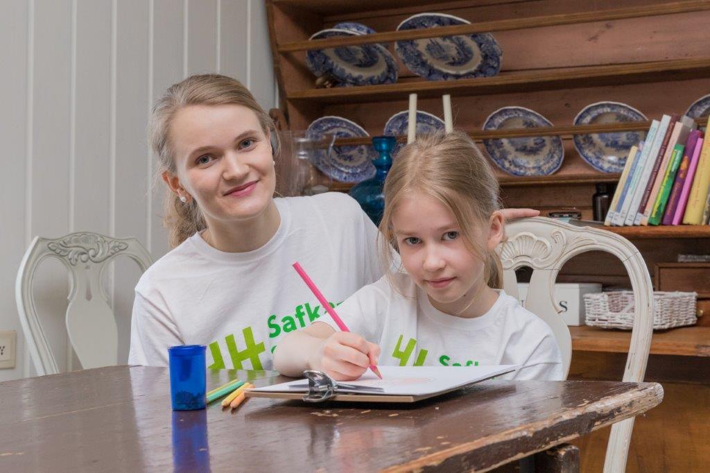 Lapsi istuu pöydän ääressä ja kirjoittaa. Aikuinen on vieressä. Molemmilla on valmoinen safkasankarit t-paita.