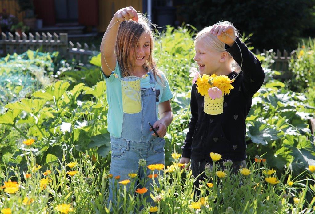Kaksi lasta kukkakedolla. He hymyilevät ja pitävät käsissään metallitölkistä askarreltuja lyhtyjä