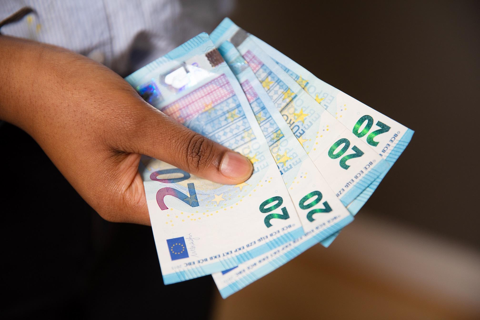 Kädessä neljä 20 euron seteliä