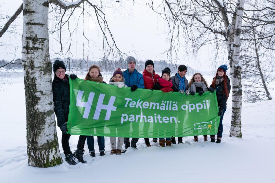 """Kuvassa on talvi. Maassa on lunta. Yhdeksän nuorta seisoo rivissä ja pitävät käsissään isoa banderollia. Banderollissa teksti """"4H. Tekemälläoppii parhaiten."""""""